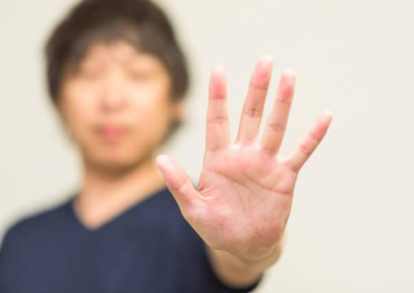 手のひらを見せる男性